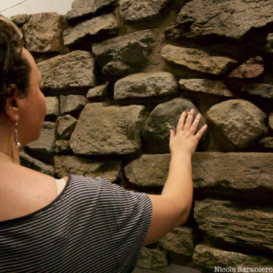 Women touching remnant of Dutch Wall