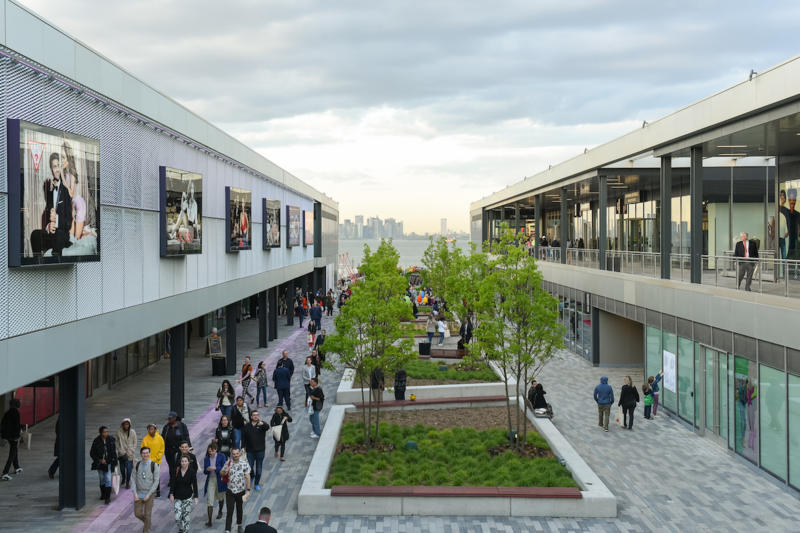 An overhead shot of the outdoor patio at Empire Outlets in Staten Island with the NYC skyline in the background