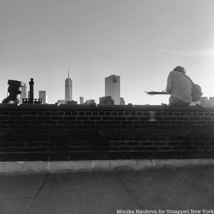 man playing guitar on rooftop