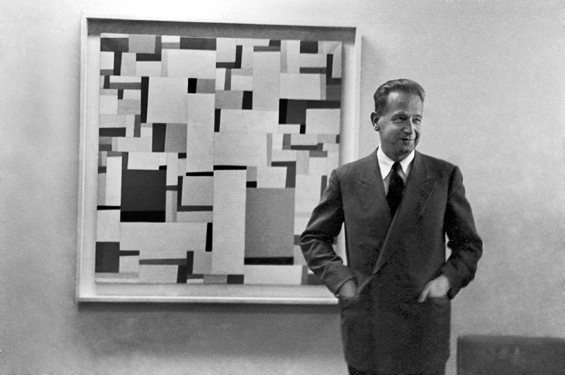 "Mr. Dag Hammarskjöld, Secretary-General of the United Nations, photographed in his outer office, on the 38th floor of the Secretariat building, standing in front of ""Rational Look,"" a geometrical abstract painting by Fritz Glarner, lent to the United Nations by New York's Museum of Modern Art. 01 March 1954"