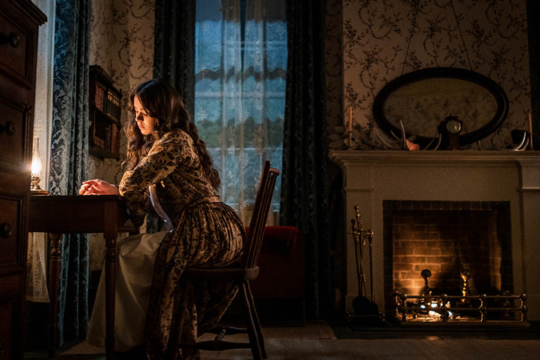 Emily Dickinson writing at her desk, played by Hailee Steinfeld